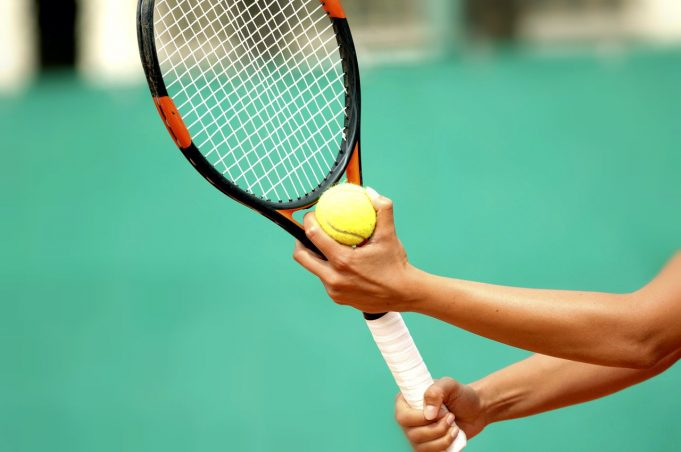 A person holding a racket and a ball