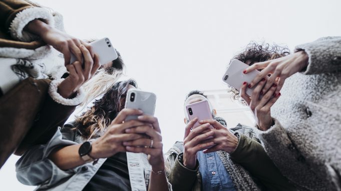 A group of people looking at a cell phone