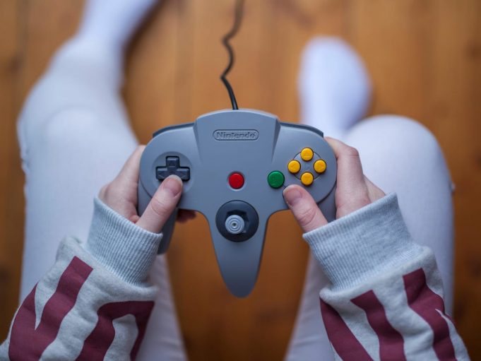 A hand holding a game remote control